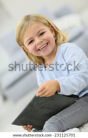 Cute little girl with tablet laughing outloud - stock photo