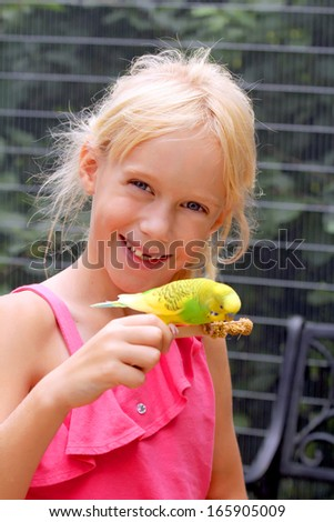 Cute little girl with the little shell parakeet - stock photo