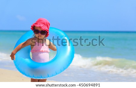 cute little girl with toy floating ring at beach - stock photo