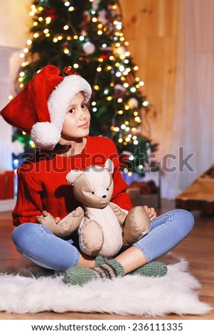 Cute little girl with toy waiting Christmas night  - stock photo