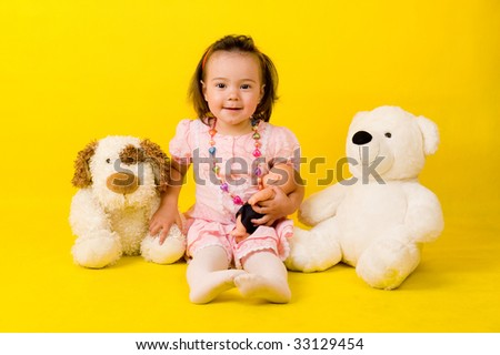 Cute little girl with toys on the floor over yellow.