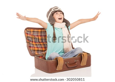 Cute little girl with two braids is isolated on white background. Girl cheerfully smiling, looking up, sitting in vintage suitcase, wearing like a pilot and pretending flying - stock photo