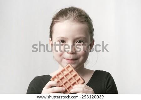 Cute little girl with waffles in the hand - stock photo