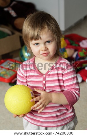 Cute little girl with yellow ball at home with toys on background