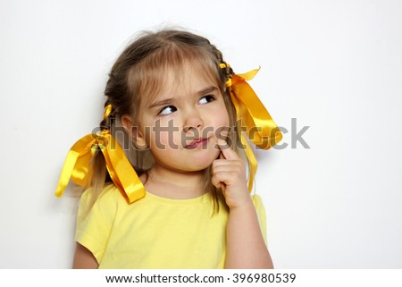 Cute little girl with yellow bows and yellow T-shirt thinking over white background, sign and gesture concept - stock photo