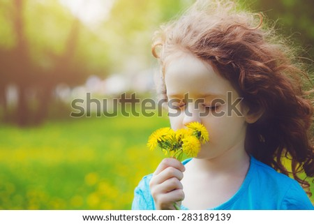 Cute little girl with yellow dandelions in the field. Background toning to instagram filter.
