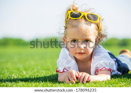 Cute little girl with yellow sun glasses on top of her head, lying on a fresh green grass in a field - stock photo