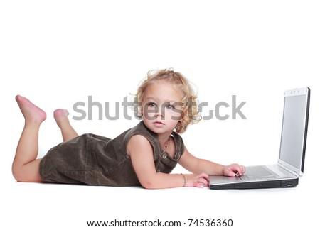 Cute little girl working on a notebook computer - stock photo