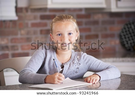 Cute little girl writing and studying in her notebook - stock photo