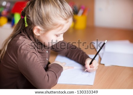 Cute little girl writing her homework at the table - stock photo