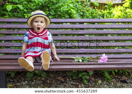 Cute little girl yawning while sitting on the bench - stock photo