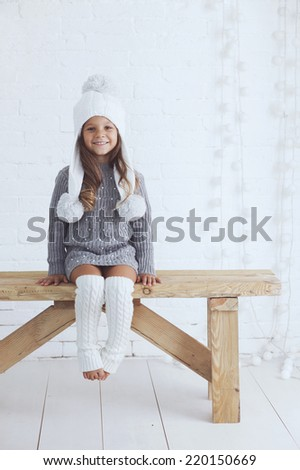 Cute little girl 5 years old wearing knitted trendy winter clothes posing over white brick wall - stock photo