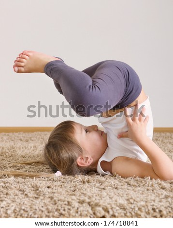Cute little girl yoga exercising at home - stock photo