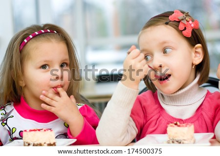 Cute little girls are eating cake in parlor - stock photo