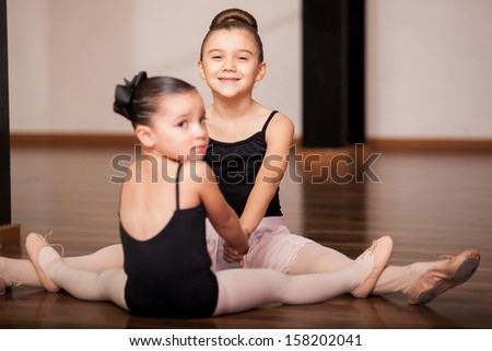 Cute little girls having fun and holding hands while doing some stretching exercises during a ballet class