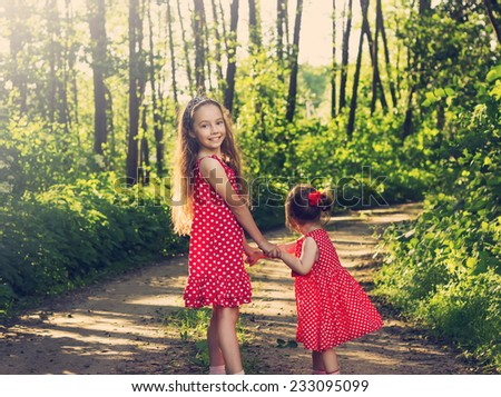 Cute little girls having fun at summer day. Toned - stock photo