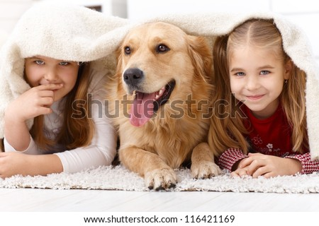Cute little girls having fun with golden retriever, lying prone on floor at home under blanket, smiling. - stock photo