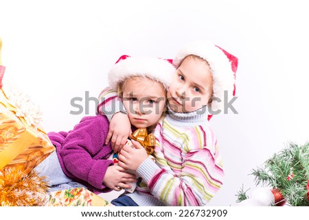 Cute little girls in Santa's hat near Christmas tree.