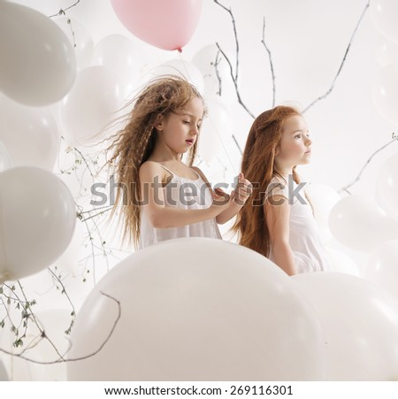 Cute little girls on balloons background - stock photo