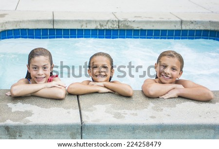 Cute little girls playing in the swimming pool - stock photo