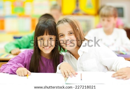 Cute little girls sitting in the classroom and smiling. Elementary age. Other kids in the background. NOTE: All the drawings and artwork in the classroom are made by children. - stock photo