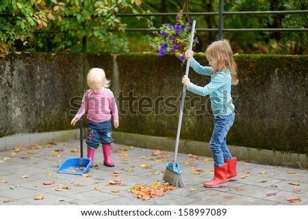 Cute little girls sweeping dry yellow leaves on autumn day - stock photo