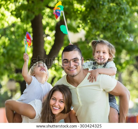Cute little girls with windmills sitting on smiling parent's arms outdoor  - stock photo