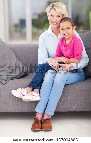 cute little granddaughter sitting on grandma's lap at home - stock photo
