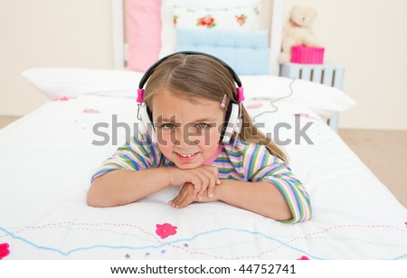 Cute little gril listening to music lying on her bed - stock photo