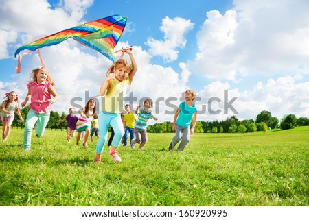 Cute little happy boys and girls running with kite together on sunny day having lot's of fun