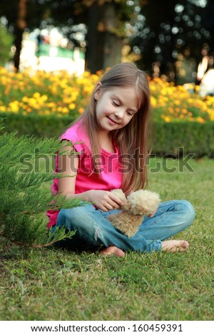 Cute little happy girl hugging brown teddy bear and sitting down on green grass meadow
