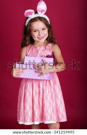 Cute little happy girl is wearing pink dress and bunny ears on red background is holding gift boxes - stock photo