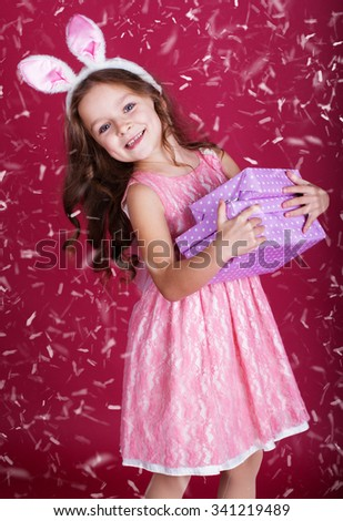 Cute little happy girl is wearing pink dress and bunny ears on red background with snow is holding gift boxes - stock photo
