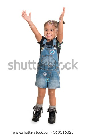 Cute little happy girl playing with bubbles over white background  - stock photo