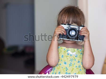 Cute little happy girl with vintage photo camera - stock photo