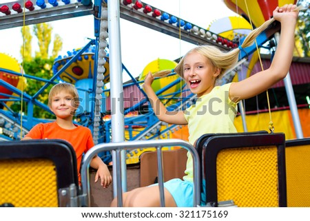Cute little happy smiling kids riding a Carnival Carousel at summer theme park - stock photo
