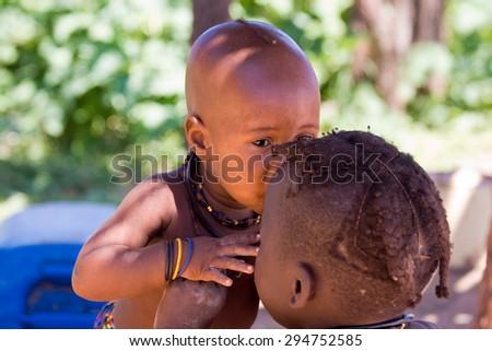 Cute little Himba boy cuddling his elderly brother. - stock photo