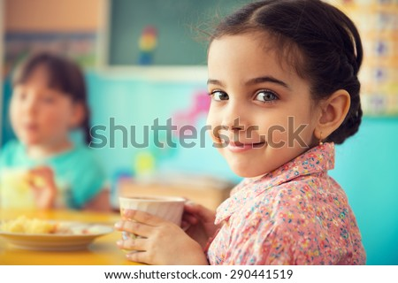 Cute little hispanic girl drinking milk at school - stock photo