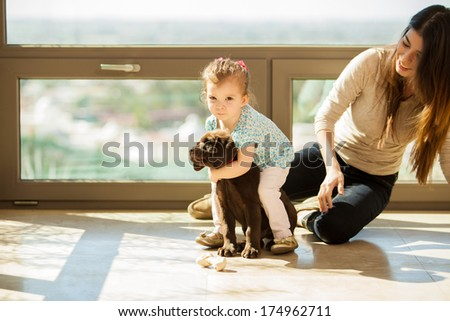 Cute little Hispanic girl giving his puppy a big hug while hanging out with her mom in the living room - stock photo