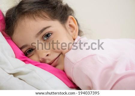 Cute little hispanic girl lying in bed - stock photo