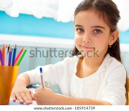 Cute little hispanic girl writing at school - stock photo