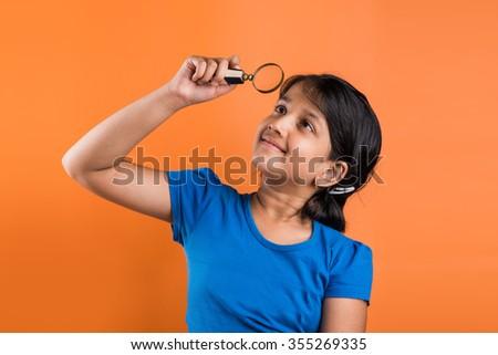 cute little indian girl looking upwards through magnifying glass, indian girl with magnifying glass, asian girl with magnifying glass, isolated over orange background - stock photo