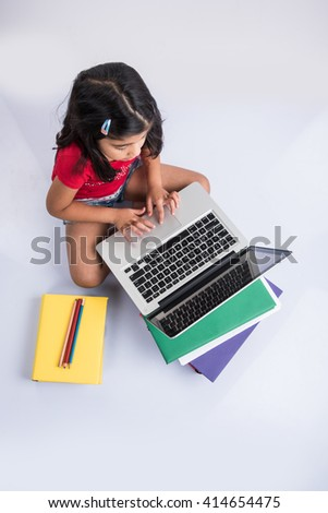 cute little indian girl studying on laptop, asian small girl studying and using laptop,  innocent indian girl child and study concept with pile of books & laptop - stock photo