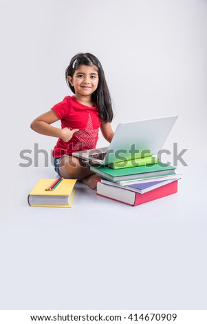 cute little indian girl studying on laptop, asian small girl studying and using laptop, innocent indian girl child and study concept with pile of books & laptop, pointing to star symbol on her T-shirt - stock photo