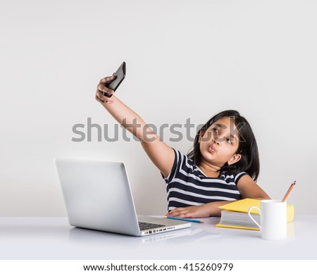 cute little indian girl taking selfie while studying on laptop - stock photo