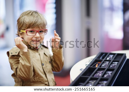 Cute little kid boy at optician store during choosing his new glasses. - stock photo