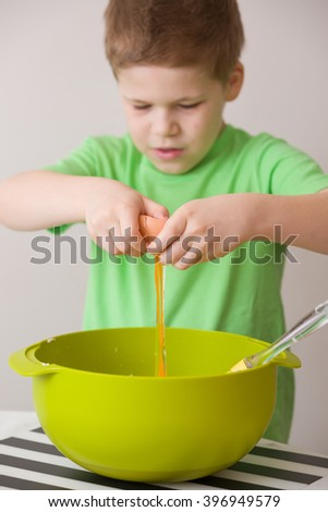 Cute little kid boy breaking an egg for the cupcake dough. Child in green t-shirt cooking in the kitchen. Indoors, on the neutral background. Learning to cook and bake with ingredients. - stock photo