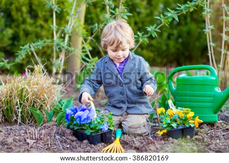 cute little kid boy helping with gardening in spring garden funny child planting flowers
