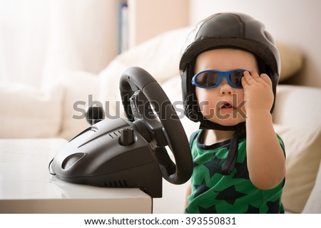Cute little kid boy in a helmet playing with Computer steering wheel. Future driver. Getting ready for professional driving. Funny toddler boy indoors. Boy and a car. - stock photo