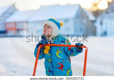 Cute little kid boy in colorful winter clothes having fun with snow shovel, outdoors during snowfall. Active outdoors leisure with children in winter. Happy child with warm hat, gloves, winter fashion - stock photo